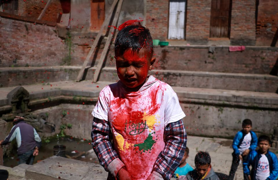 A boy with red colored allover his face image