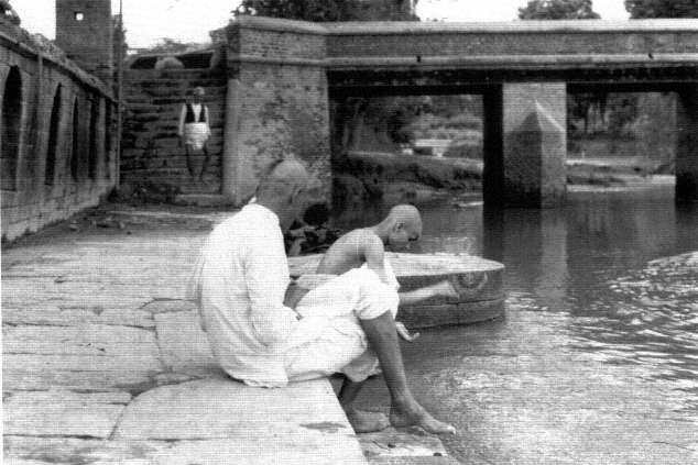 Rajopadhyaya Brahmans in a purification ceremony at the river image