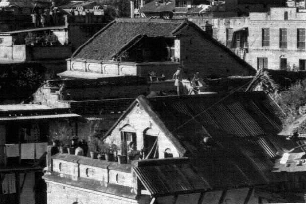 Standing on the kasis the open roof porches of houses, men fly kites during Mohani image