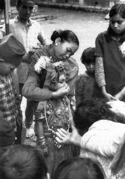 The living goddess Kumari has her running nose wiped by her attendant image