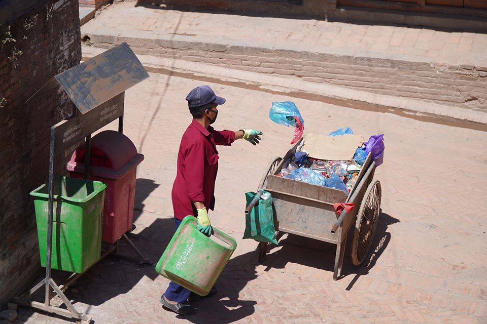 Worker taking wastage from dustbin image