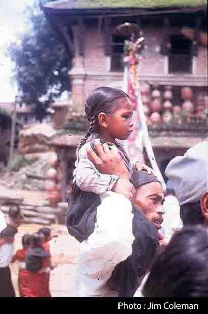 carrying his daughter on his shoulders during the Gaijatra image