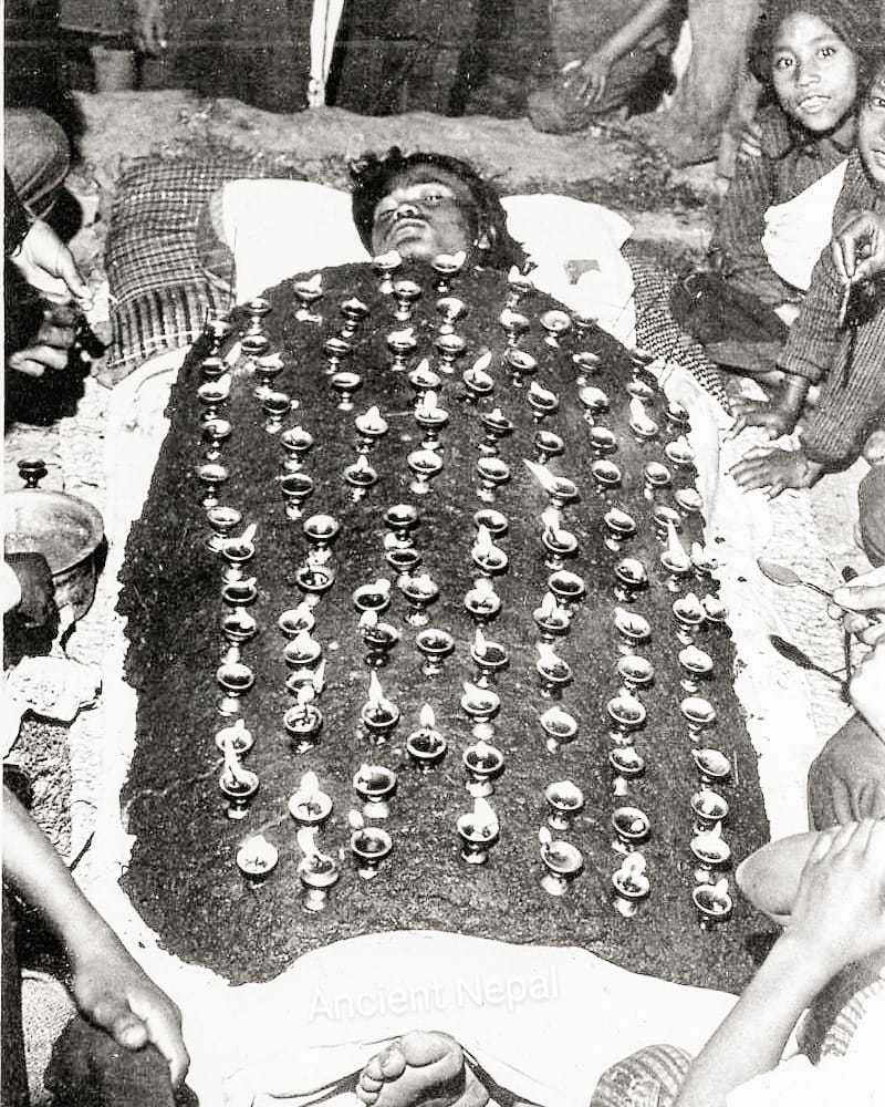 devotee lying under oil lamps on a blanket of cow dung at Dasain in 1977 image